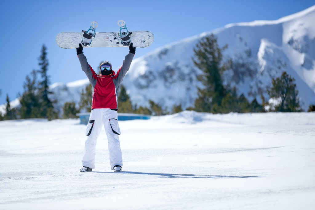 Happy snowboarder holding snowboard over head