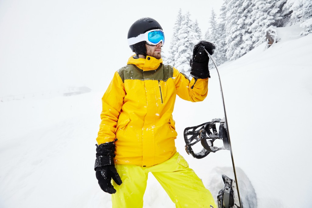 Close up portrait of male snowboarder wearing helmet with glasse