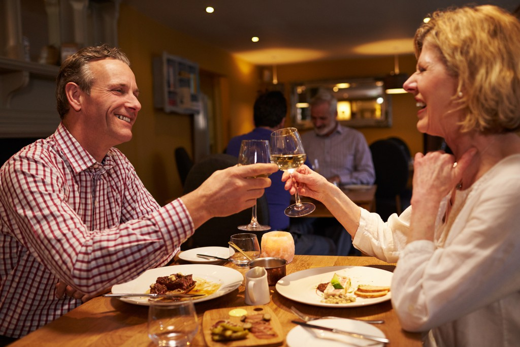 Senior couple making a toast at a meal in a restaurant
