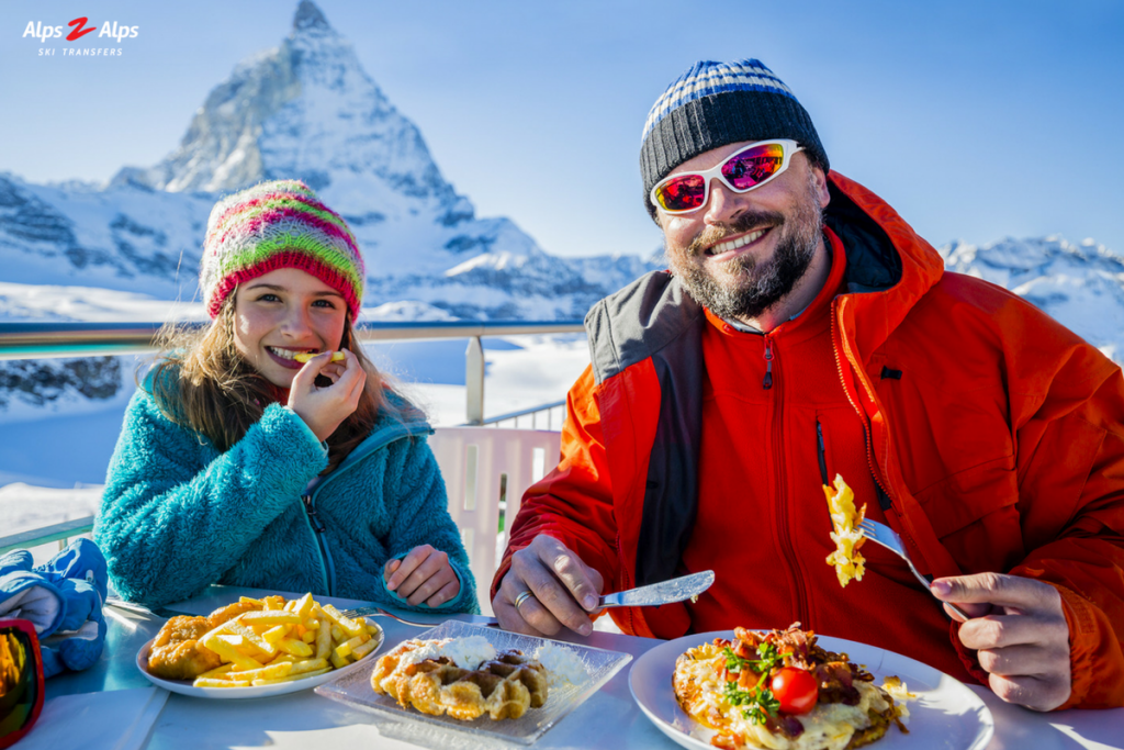 Father and daughter eating in the alps