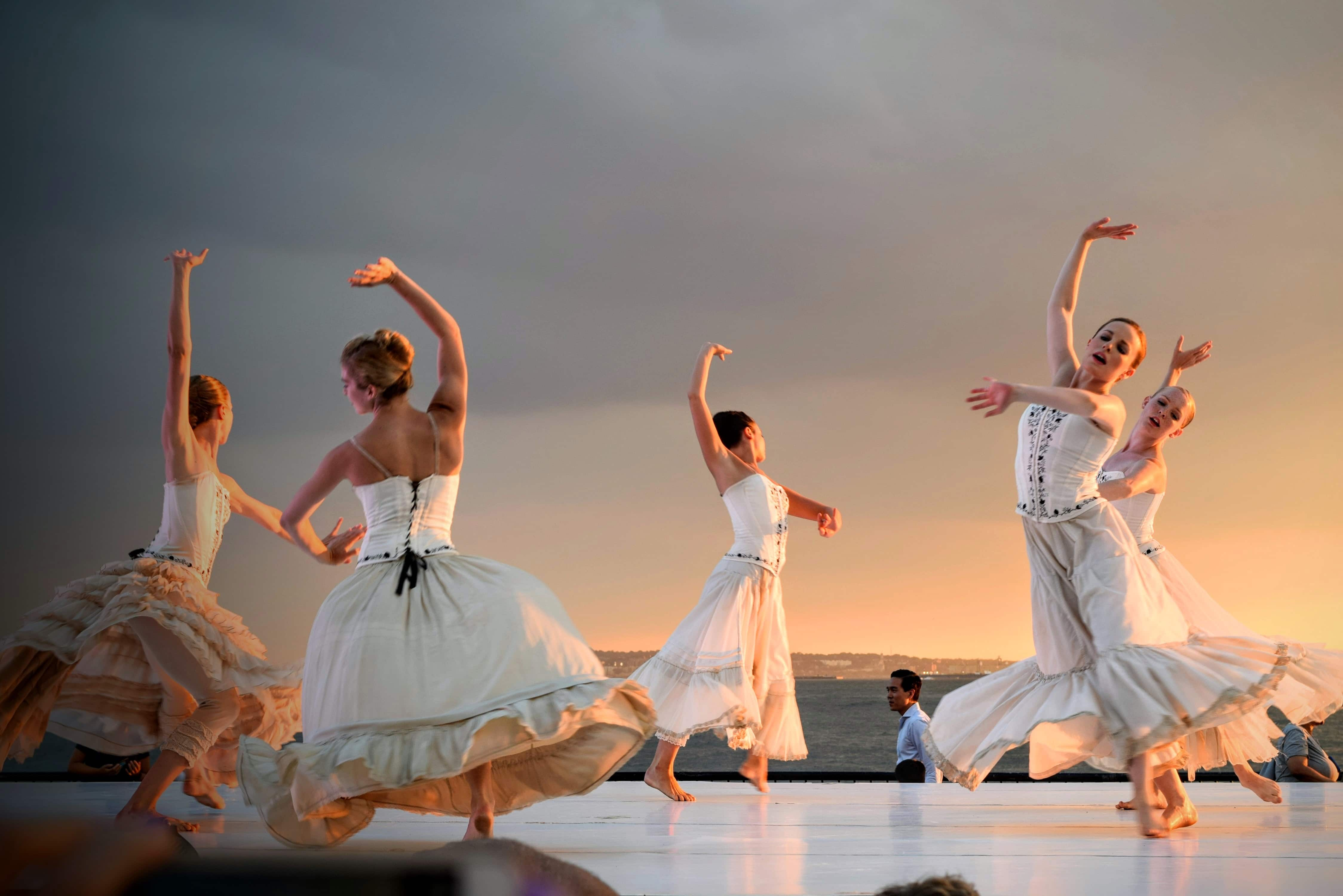 Dancers dressed in white on stage, with the sea in the background.