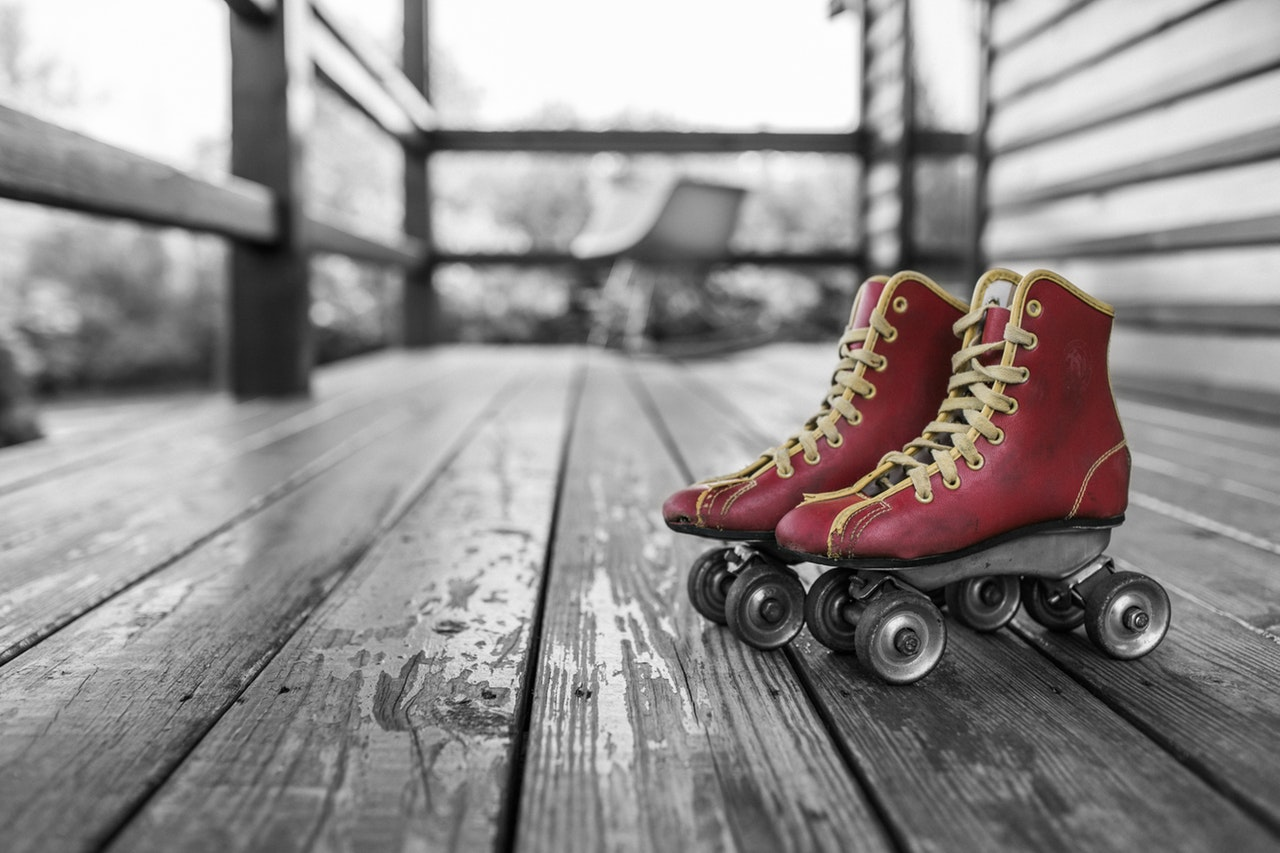 Red vintage roller blades on a porch, against a black and white background.
