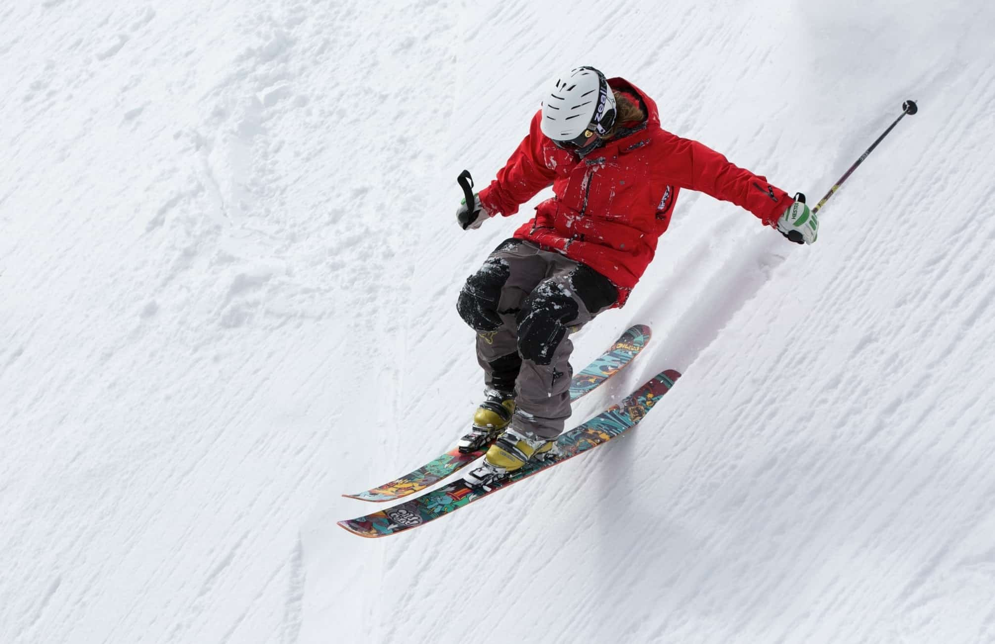 Skier in red skiing down steep slode