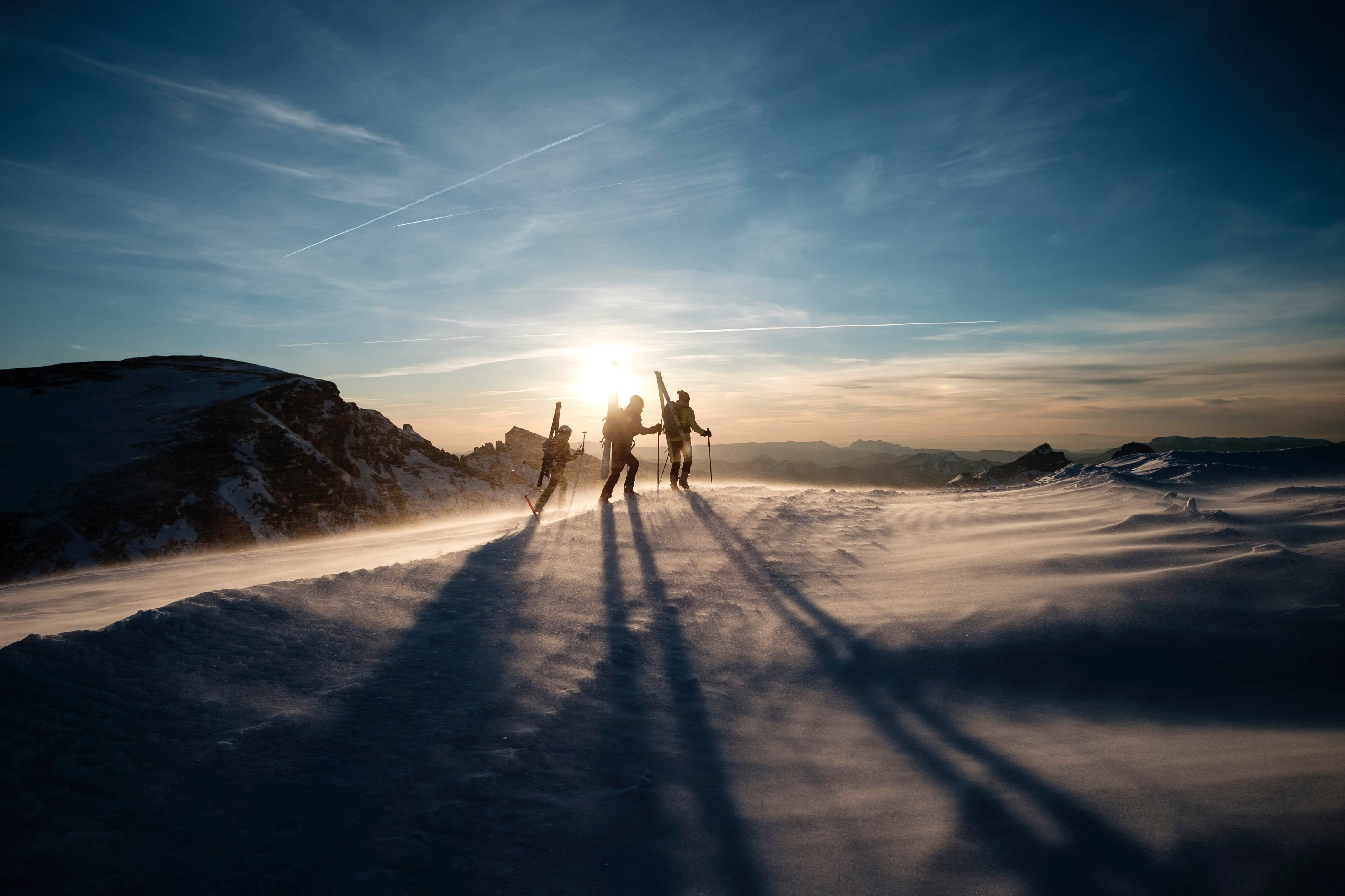 Three skiers walking as the sun starts to set