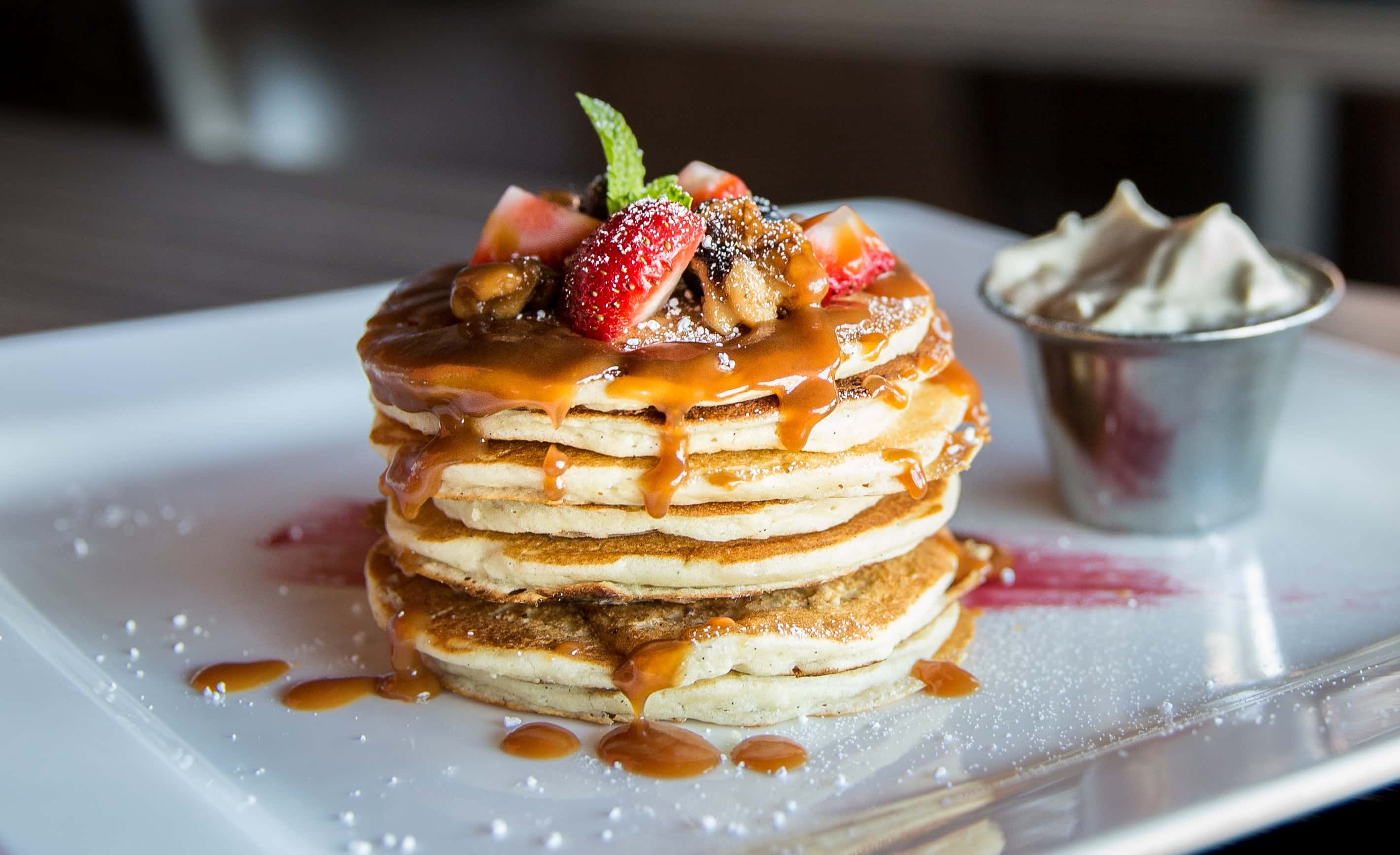 Waffles with syrup and fruit on top.