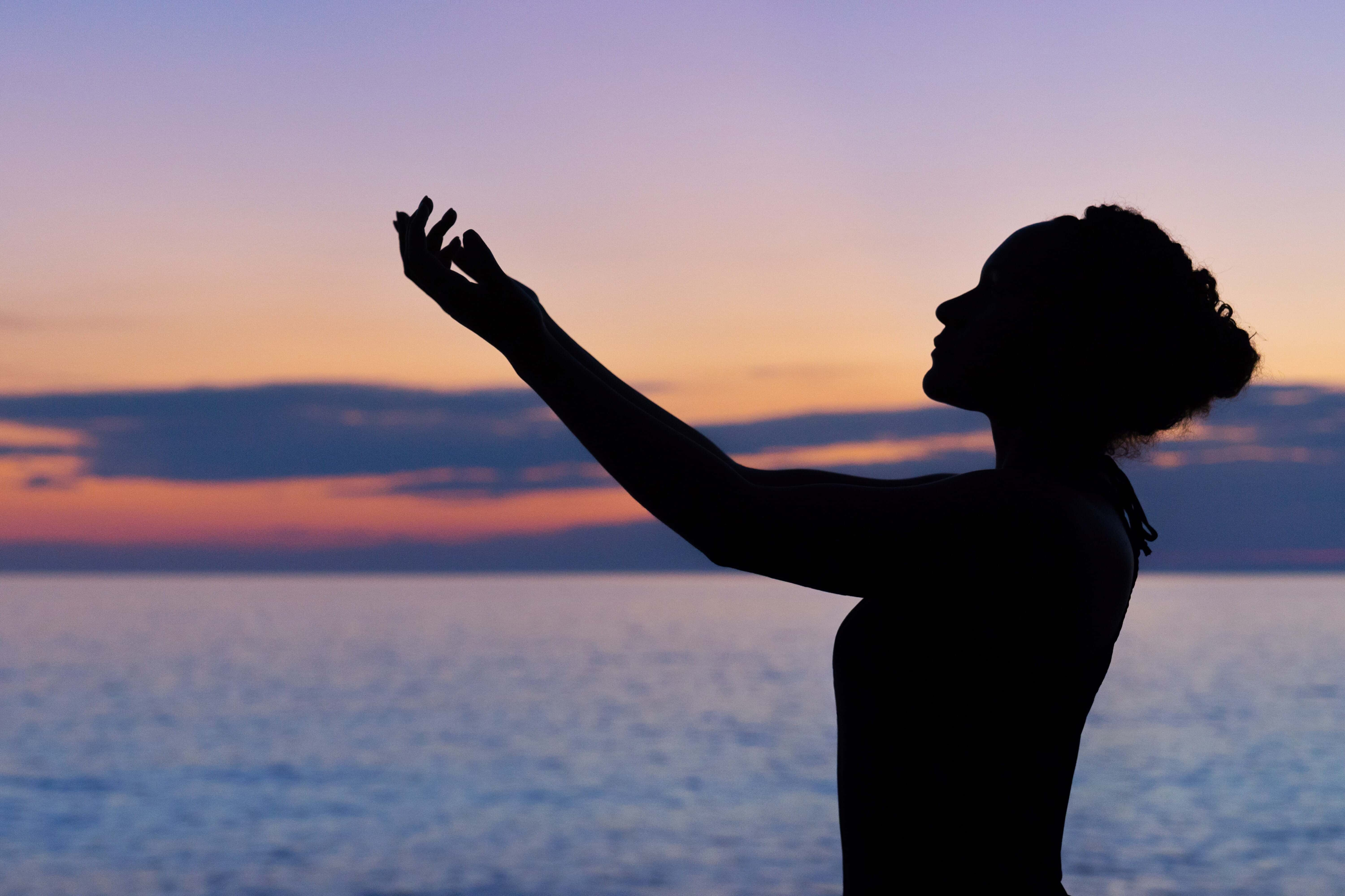 Silhouette of woman practising yoga in front of the sea.
