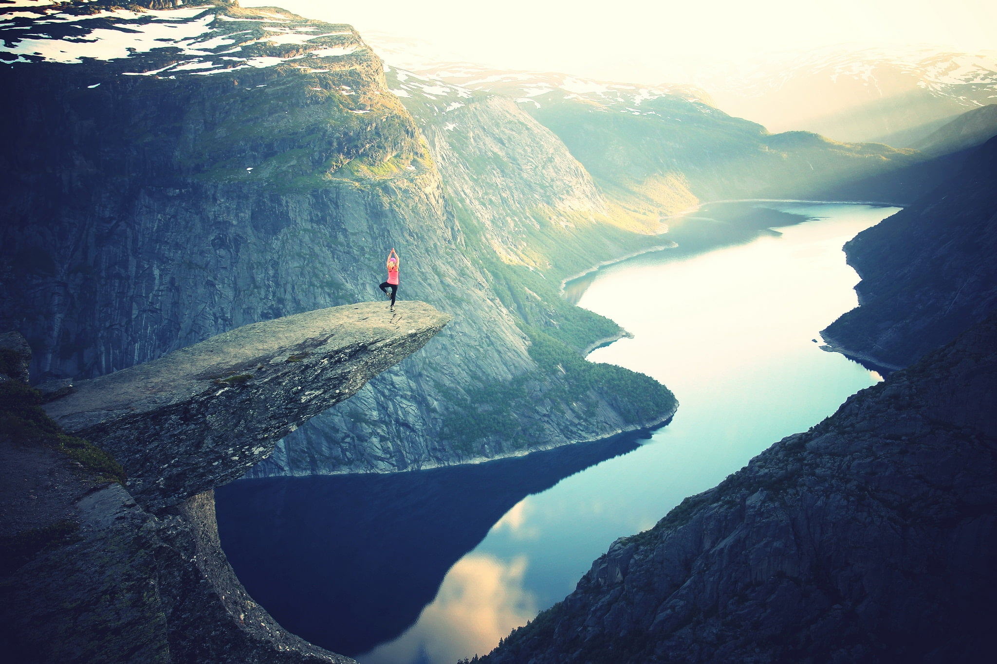 Woman on a high mountain ledge overlooking a river.