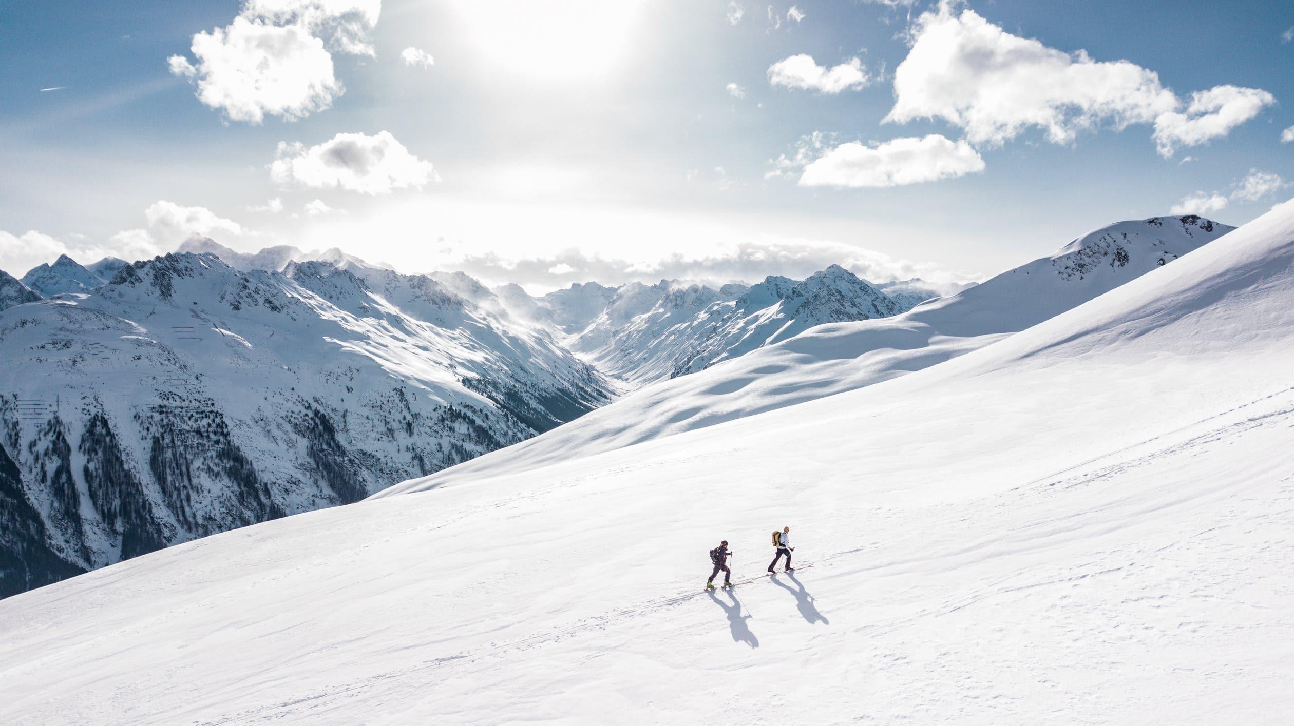 Skiers walking up large slope