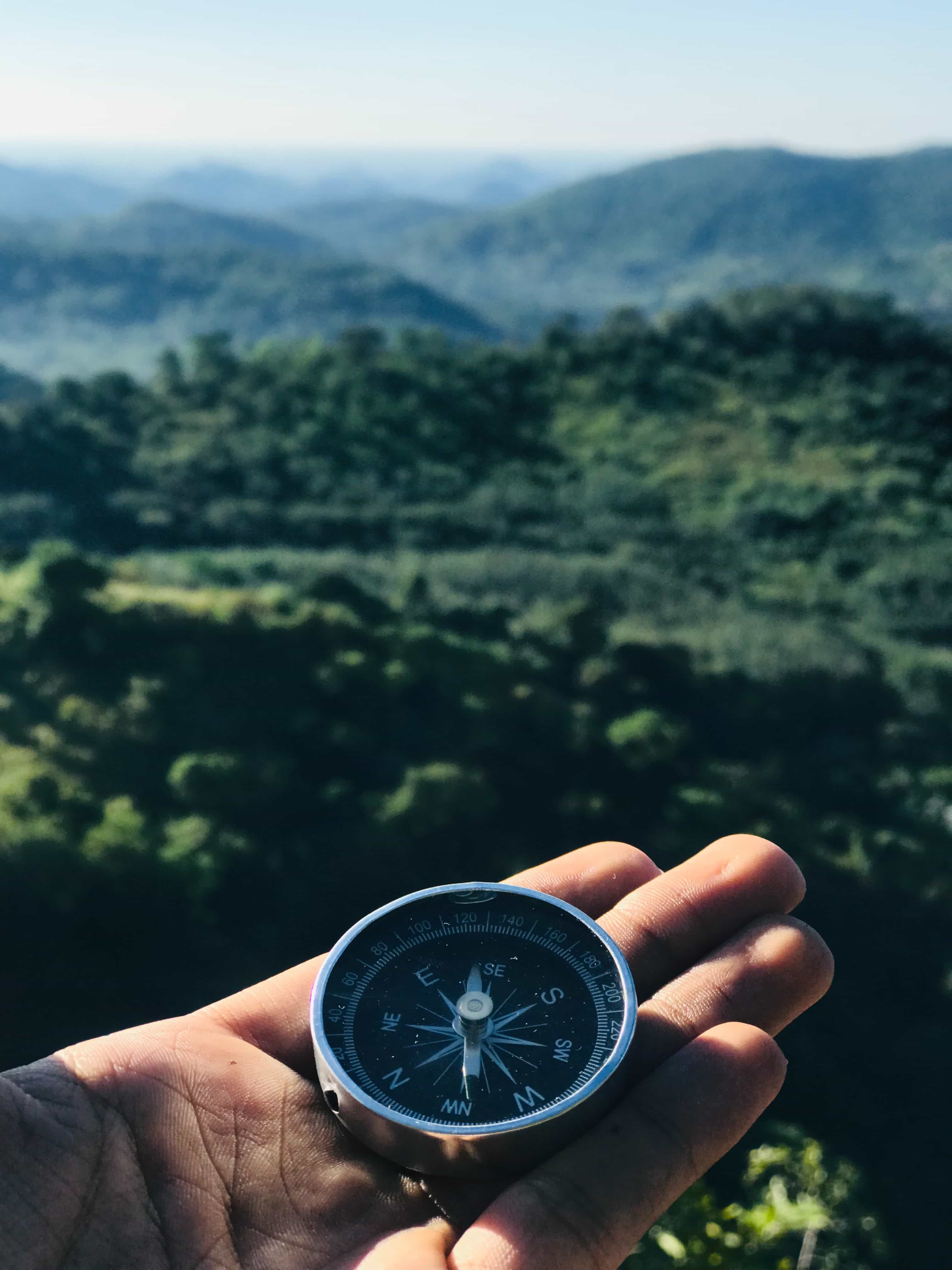 Person holding compass in an Alpine valley