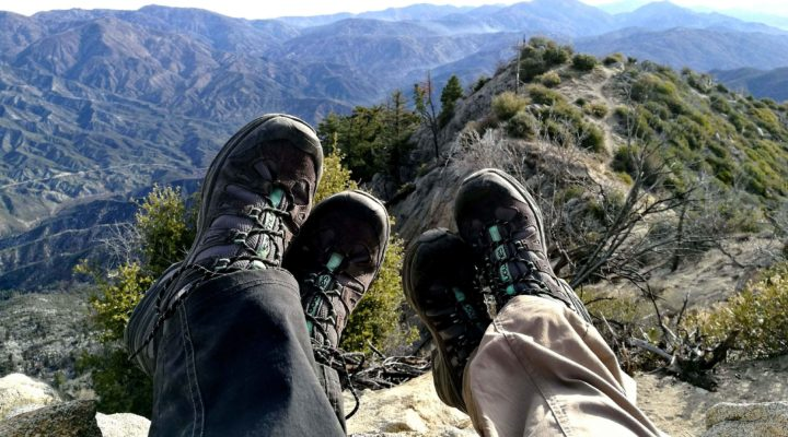 Two pairs of feet in hiking boots at the top of a mountain