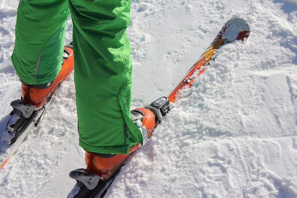 Close up of person wearing pair of skis in snow