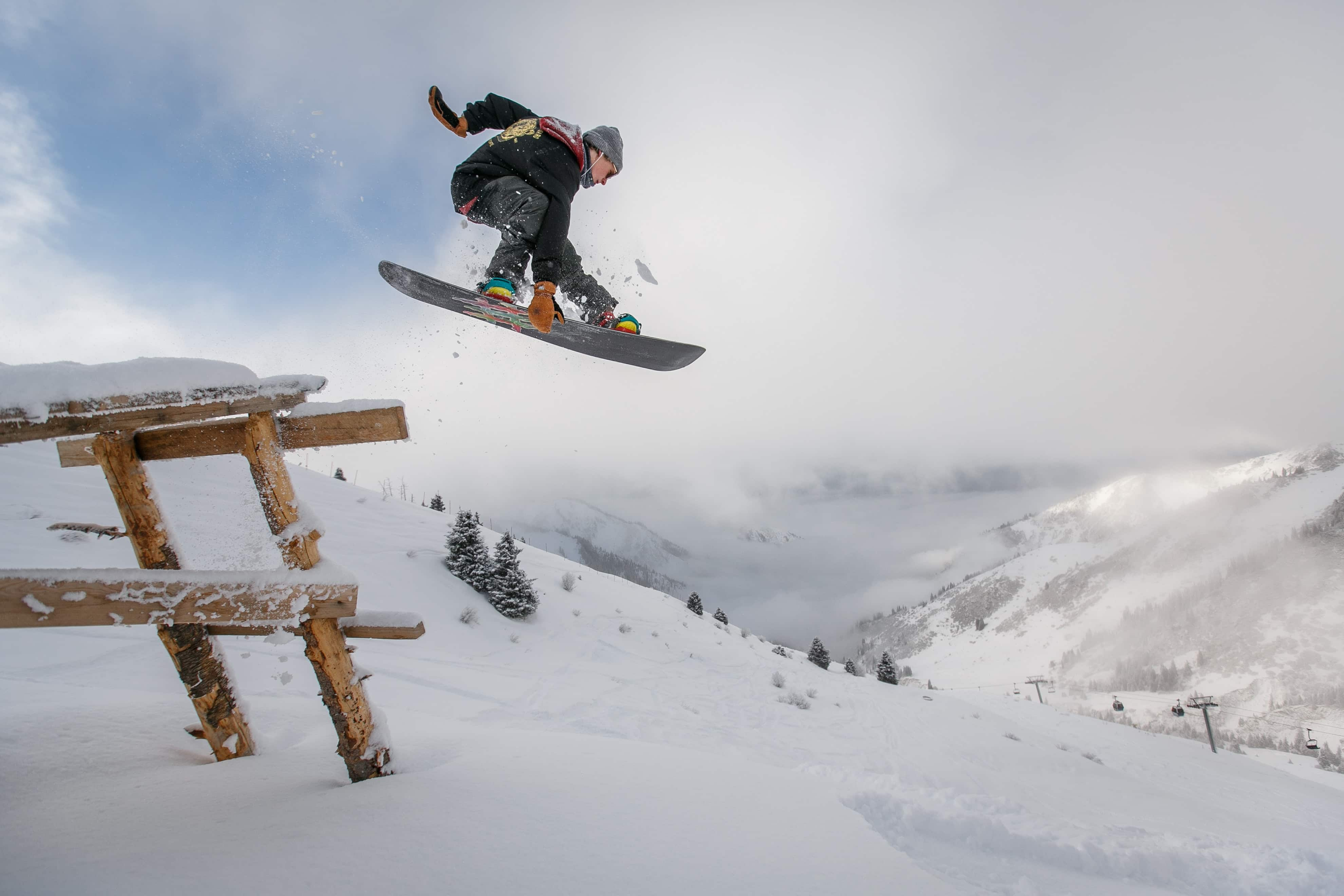 Snowboarder jumping over wooden bench in snow