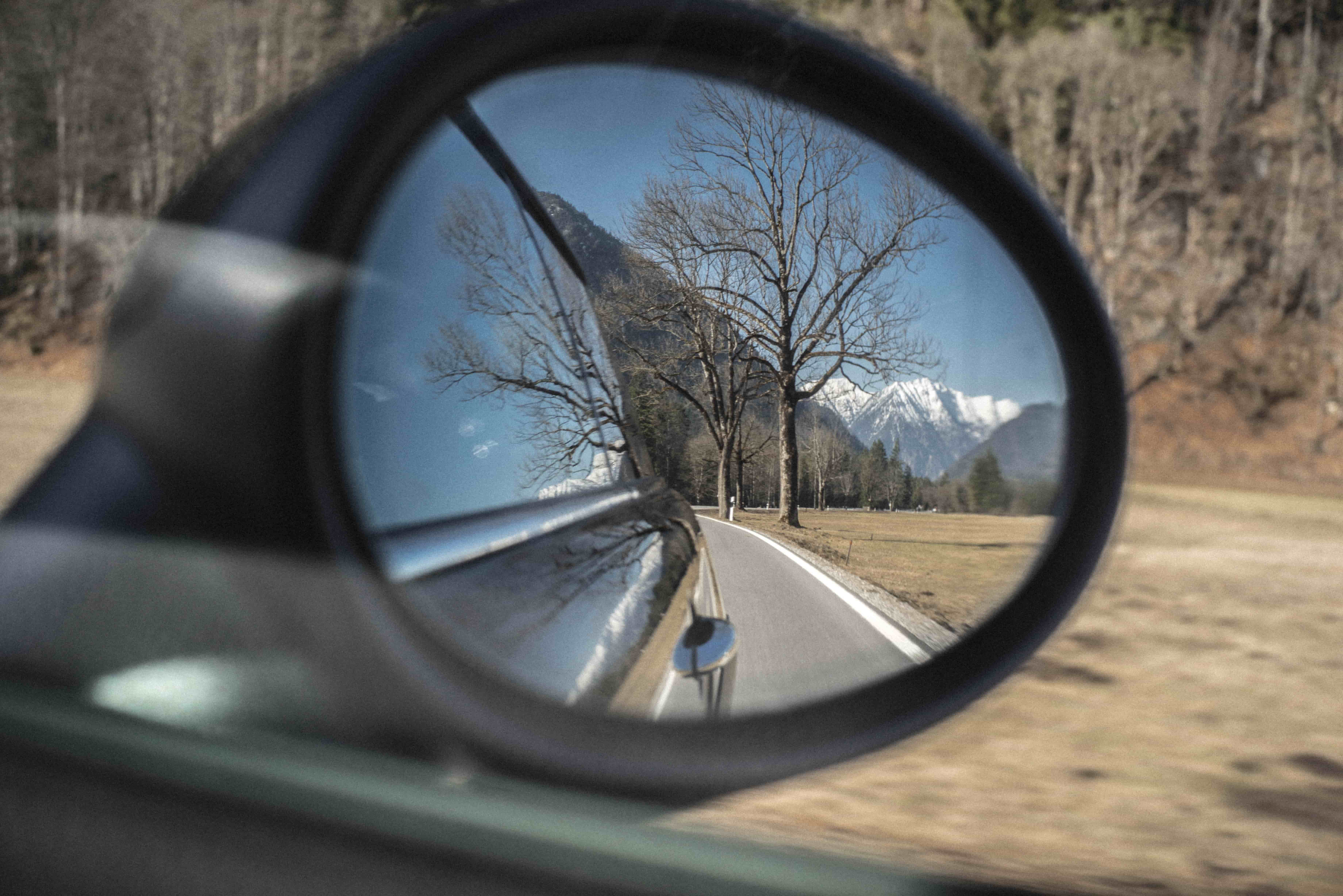 View of the Alps from car wing mirror