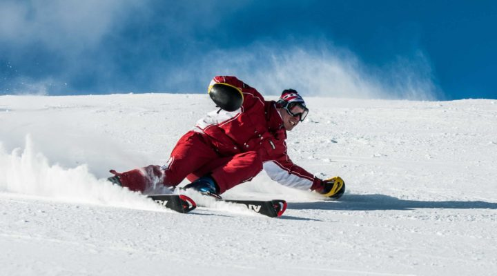 Man in red skiing down a slope