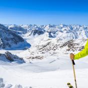 Skier overlooking snowy mountain peaks