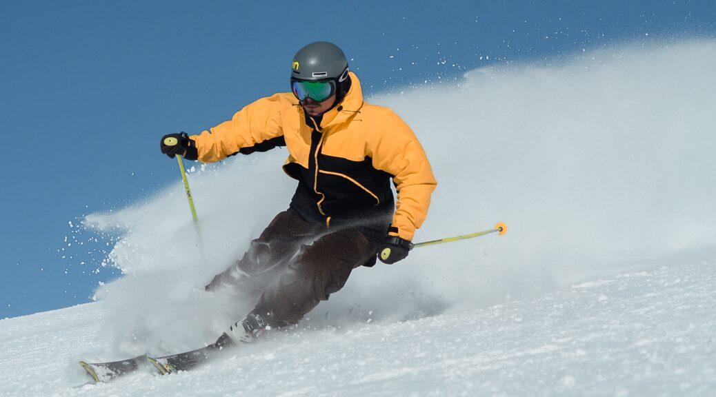 Man skiiing down mountain wearing a yellow and black ski jacket